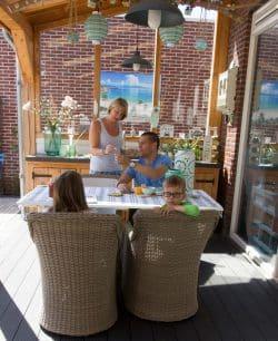 Gezin aan tafel in de veranda